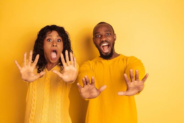 Jeune homme afro-américain émotionnel et femme dans des vêtements décontractés lumineux sur l'espace jaune