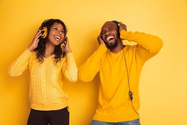 Jeune homme afro-américain émotionnel et femme sur jaune