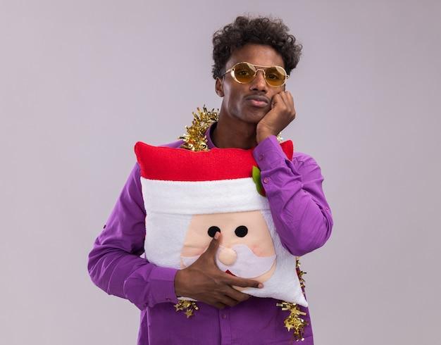 Jeune homme afro-américain ennuyé portant des lunettes avec une guirlande de guirlandes autour du cou tenant un oreiller du père noël en gardant la main sur le menton en regardant la caméra isolée sur fond blanc