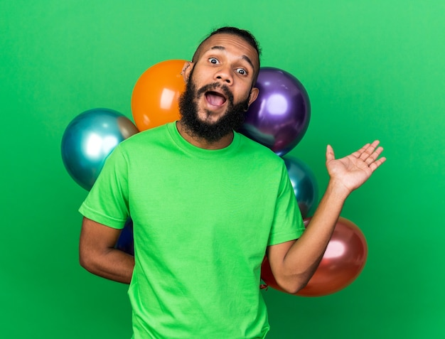 Jeune homme afro-américain excité portant un t-shirt vert debout devant des ballons écartant la main isolée sur un mur vert