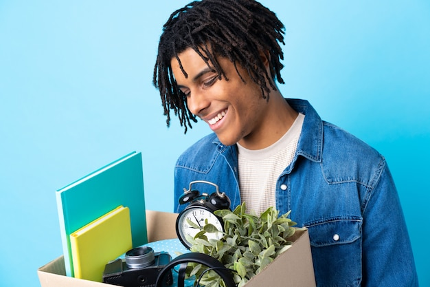 Jeune homme afro-américain faisant un geste tout en ramassant une boîte pleine de choses