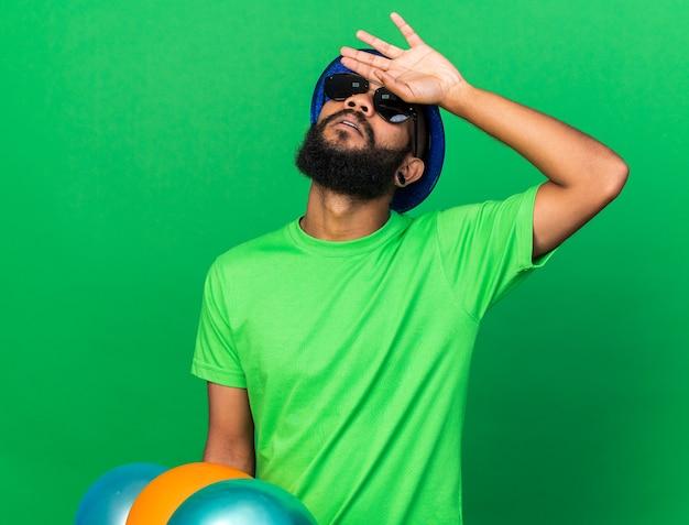 Jeune homme afro-américain fatigué portant un chapeau de fête et des lunettes tenant des ballons mettant la main sur le front isolé sur un mur vert