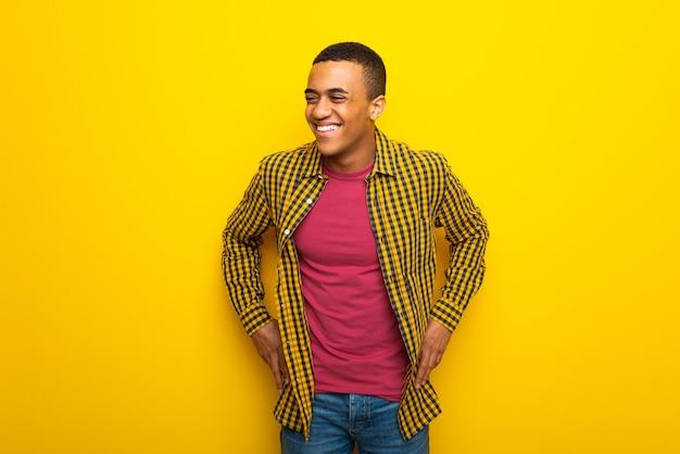 Jeune homme afro américain sur fond jaune, heureux et souriant