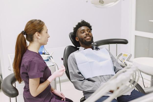Jeune homme afro-américain. guy visitant le cabinet du dentiste pour la prévention de la cavité buccale. homme et médecin de famille pendant le contrôle des dents.