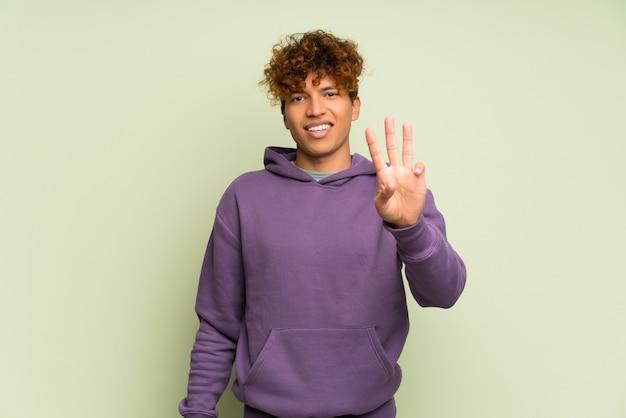 Jeune homme afro-américain heureux et comptant trois avec les doigts