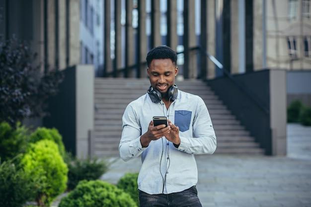 Jeune homme afro-américain heureux de gagner regarde le téléphone se réjouit et sourit dans des vêtements décontractés