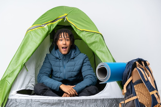 Jeune homme afro-américain à l'intérieur d'une tente de camping verte avec une expression faciale surprise