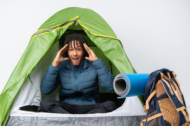 Jeune homme afro-américain à l'intérieur d'une tente de camping verte avec expression surprise