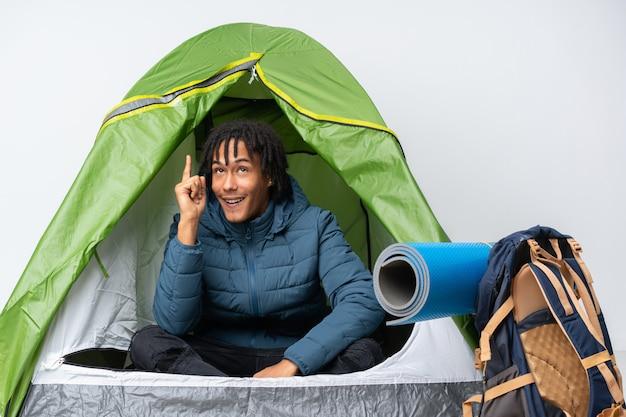 Jeune homme afro-américain à l'intérieur d'une tente verte de camping dans l'intention de réaliser la solution tout en levant un doigt