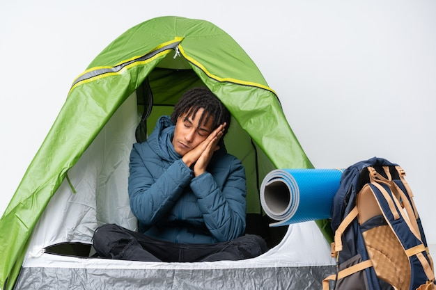 Jeune homme afro-américain à l'intérieur d'une tente verte de camping faisant un geste de sommeil dans une expression dorable