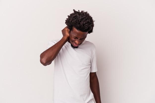 Jeune homme afro-américain isolé sur fond blanc ayant une douleur au cou due au stress, en le massant et en le touchant avec la main.