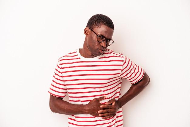 Jeune homme afro-américain isolé sur fond blanc ayant une douleur au foie, des maux d'estomac.