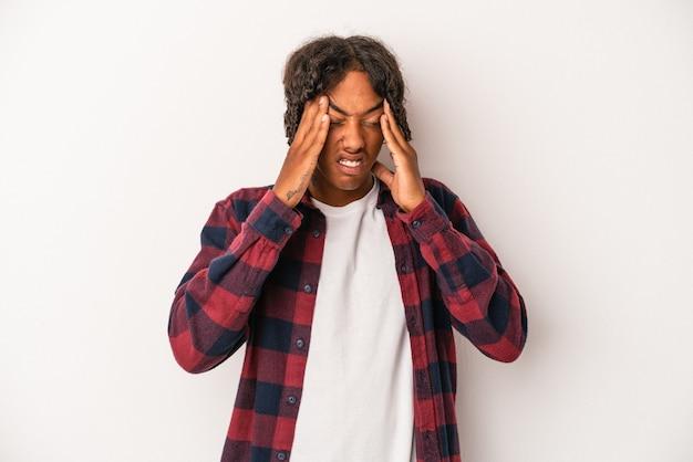 Jeune homme afro-américain isolé sur fond blanc ayant un mal de tête, touchant le devant du visage.