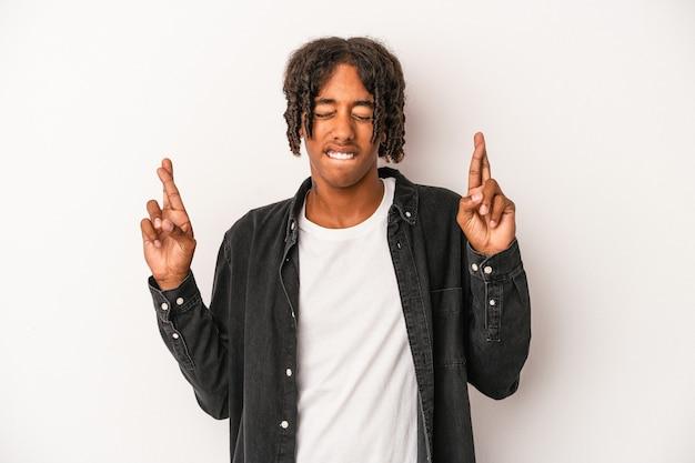 Jeune homme afro-américain isolé sur fond blanc croisant les doigts pour avoir de la chance