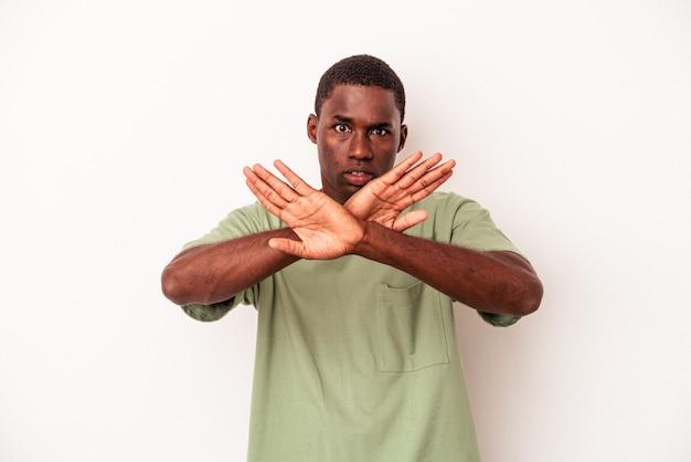 Jeune homme afro-américain isolé sur fond blanc faisant un geste de déni