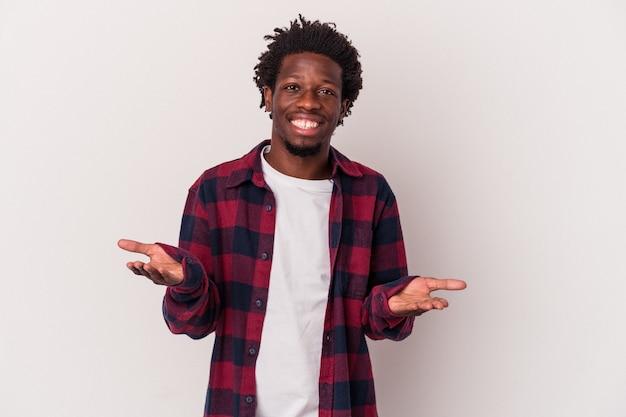 Jeune homme afro-américain isolé sur fond blanc fait de l'échelle avec les bras, se sent heureux et confiant.