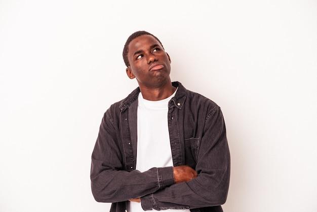 Jeune homme afro-américain isolé sur fond blanc fatigué d'une tâche répétitive.