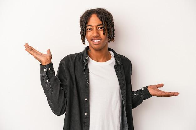 Jeune homme afro-américain isolé sur fond blanc haussant les épaules confus et douteux pour tenir un espace de copie.