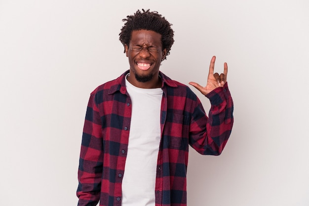 Jeune homme afro-américain isolé sur fond blanc montrant un geste rock avec les doigts
