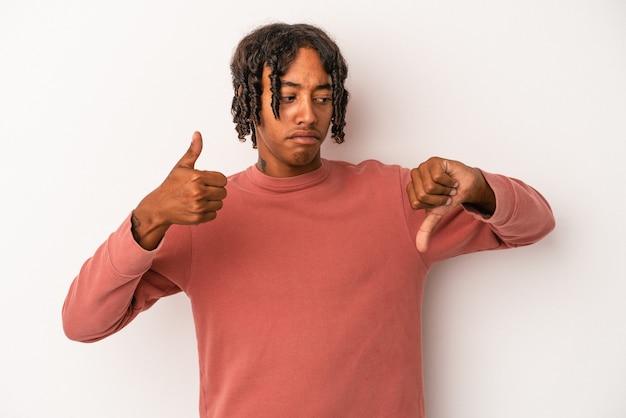 Jeune homme afro-américain isolé sur fond blanc montrant les pouces vers le haut et les pouces vers le bas, concept difficile à choisir
