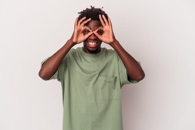 Jeune homme afro-américain isolé sur fond blanc montrant un signe d'accord sur les yeux
