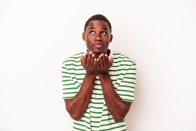 Jeune homme afro-américain isolé sur fond blanc pliant les lèvres et tenant les paumes pour envoyer un baiser aérien.