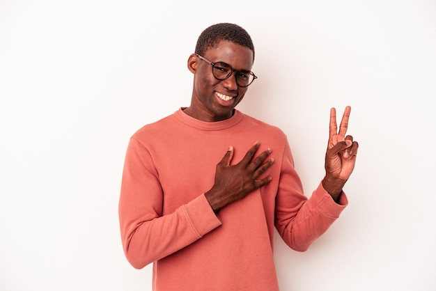 Jeune homme afro-américain isolé sur fond blanc prêtant serment, mettant la main sur la poitrine.
