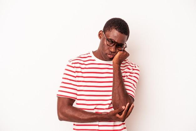 Jeune homme afro-américain isolé sur fond blanc qui se sent triste et pensif, regardant l'espace de copie.