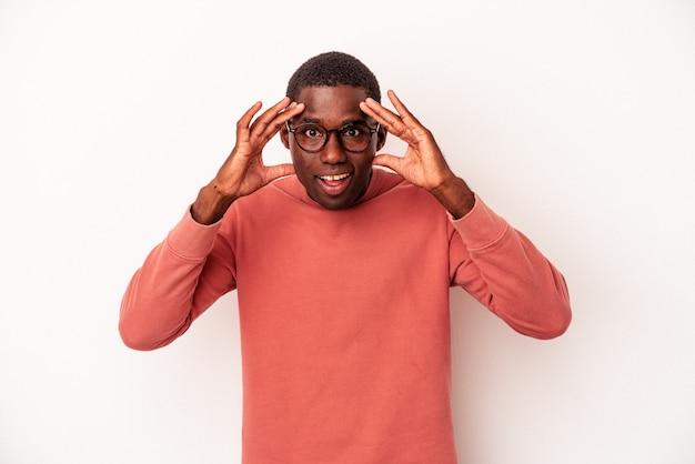 Jeune homme afro-américain isolé sur fond blanc recevant une agréable surprise, excité et levant les mains.