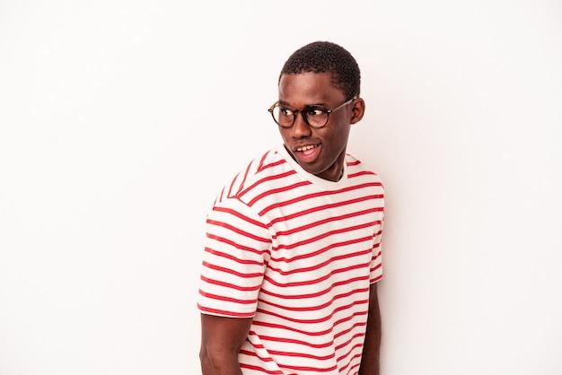 Jeune homme afro-américain isolé sur fond blanc regarde de côté souriant, joyeux et agréable.