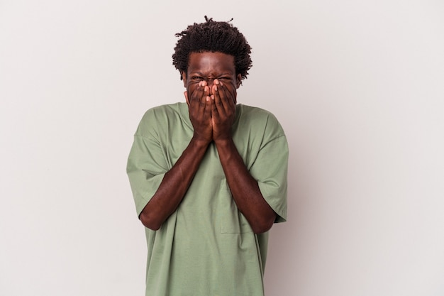 Jeune homme afro-américain isolé sur fond blanc en riant de quelque chose, couvrant la bouche avec les mains.