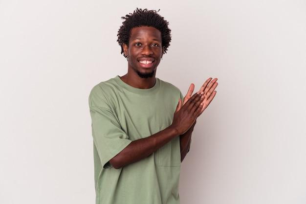 Jeune homme afro-américain isolé sur fond blanc se sentant énergique et confortable, se frottant les mains confiant.