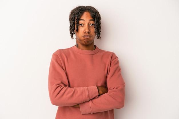 Jeune homme afro-américain isolé sur fond blanc souffle les joues, a une expression fatiguée. concept d'expression faciale.