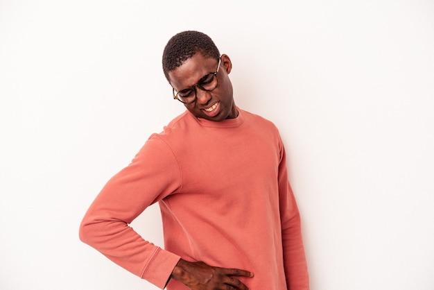 Jeune homme afro-américain isolé sur fond blanc souffrant d'un mal de dos.