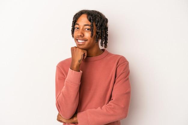 Jeune homme afro-américain isolé sur fond blanc souriant heureux et confiant, touchant le menton avec la main.