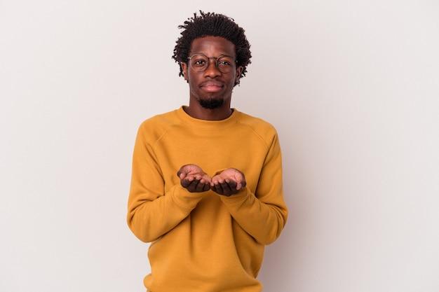 Jeune homme afro-américain isolé sur fond blanc tenant quelque chose avec des paumes, offrant à la caméra.