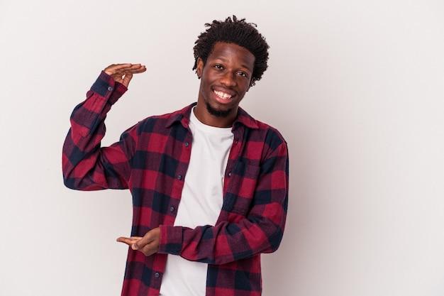Jeune homme afro-américain isolé sur fond blanc tenant quelque chose de petit avec les index, souriant et confiant.