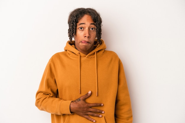 Jeune homme afro-américain isolé sur fond blanc touche le ventre, sourit doucement, concept de manger et de satisfaction.