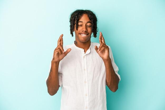 Jeune homme afro-américain isolé sur fond bleu croisant les doigts pour avoir de la chance