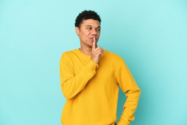 Jeune homme afro-américain isolé sur fond bleu montrant un signe de silence geste mettant le doigt dans la bouche