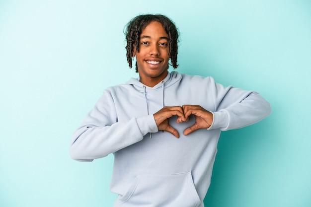 Jeune homme afro-américain isolé sur fond bleu souriant et montrant une forme de coeur avec les mains.