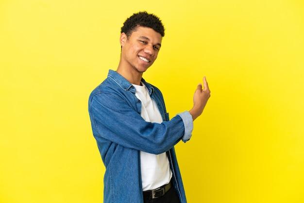 Jeune homme afro-américain isolé sur fond jaune pointant vers l'arrière