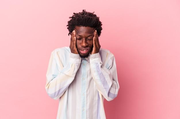 Jeune homme afro-américain isolé sur fond rose ayant un mal de tête, touchant le devant du visage.