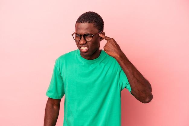 Jeune homme afro-américain isolé sur fond rose couvrant les oreilles avec les mains.