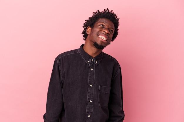 Jeune homme afro-américain isolé sur fond rose dansant et s'amusant.