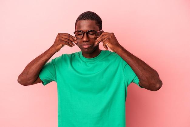 Jeune homme afro-américain isolé sur fond rose doutant entre deux options.