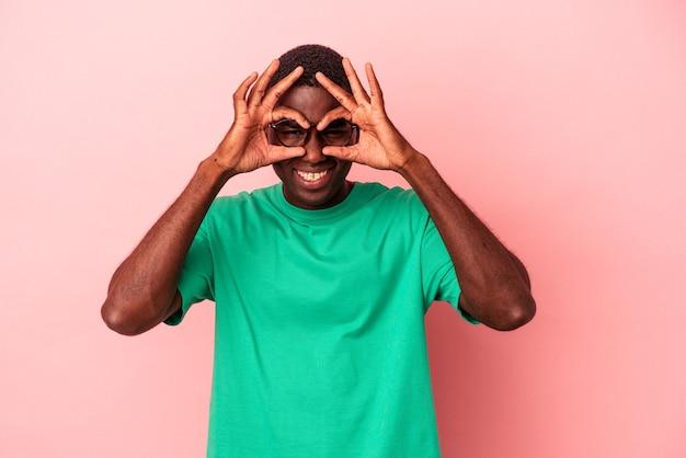 Jeune homme afro-américain isolé sur fond rose excité en gardant le geste ok sur les yeux.