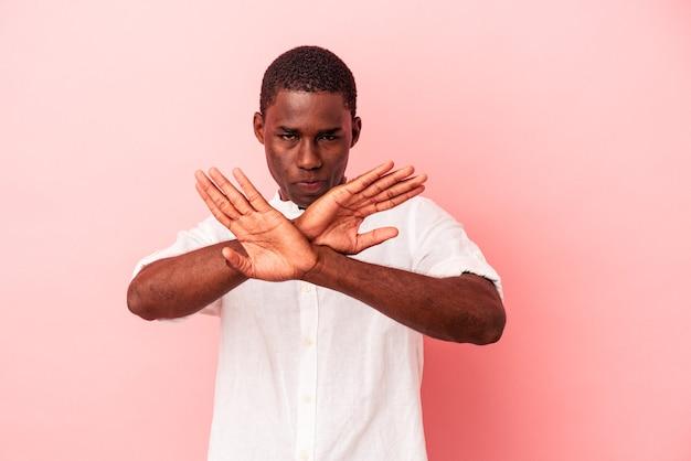 Jeune homme afro-américain isolé sur fond rose faisant un geste de déni