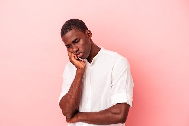 Jeune homme afro-américain isolé sur fond rose fatigué d'une tâche répétitive.