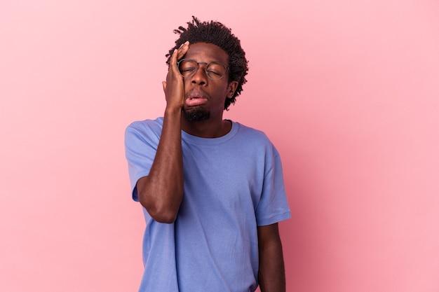 Jeune homme afro-américain isolé sur fond rose fatigué et très endormi en gardant la main sur la tête.